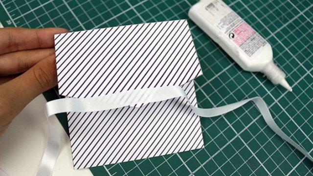 Cole a fita de cetim na aba do envelope assim como na foto.